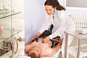 Female physician performing ECG test